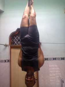 HANGING UPSIDE DOWN FROM AN IRON LOOP